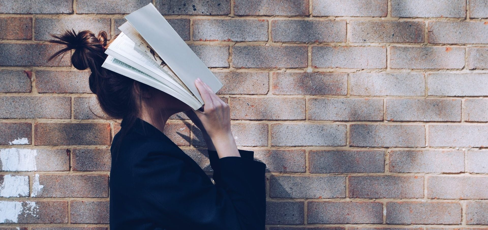 Woman covering face with a book