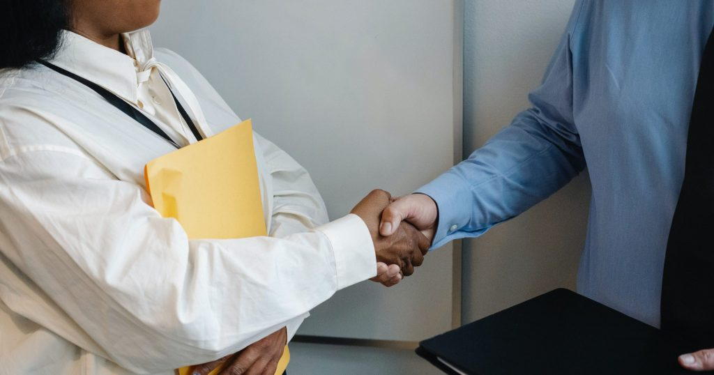 Image of people shaking hands in office