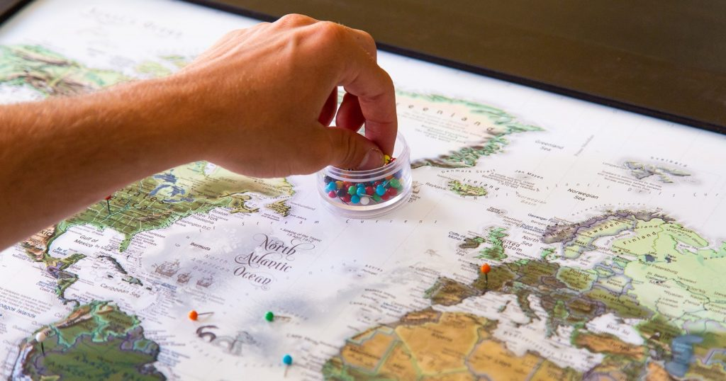 Person placing push pins into World Map.