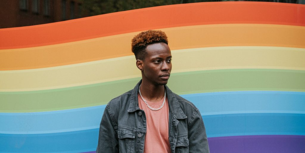 Contemplative black man standing against window painted in lgbt colors