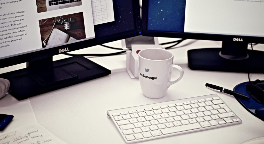 White ceramic mug between apple magic keyboard and two flat screen computer monitors