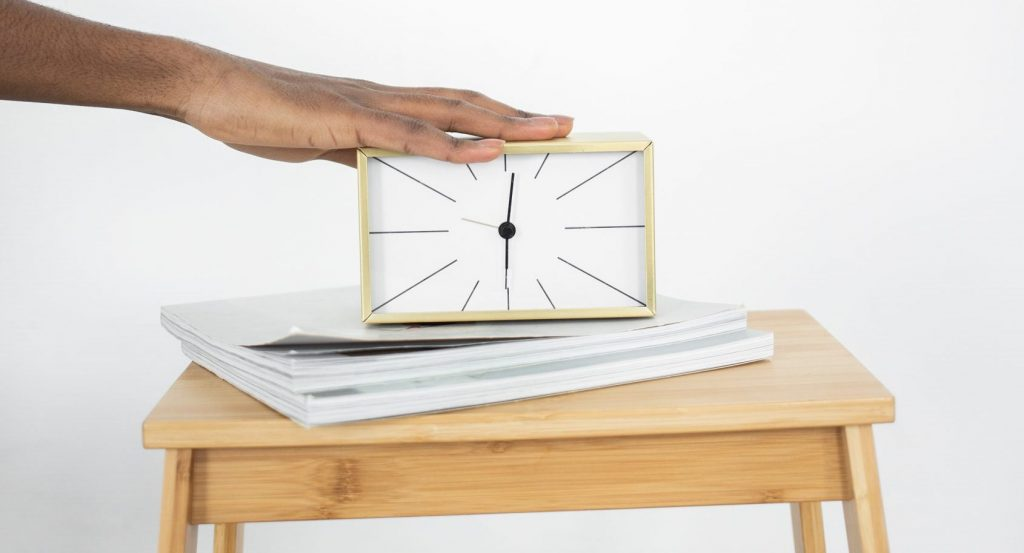 A person touching an analog clock on a wooden table