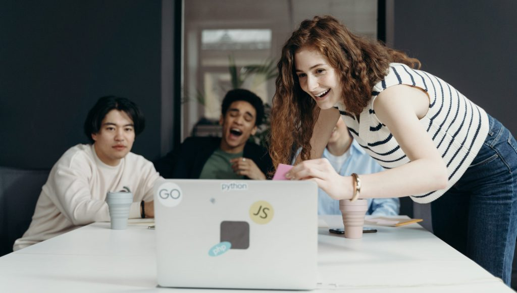 People laughing looking at a laptop