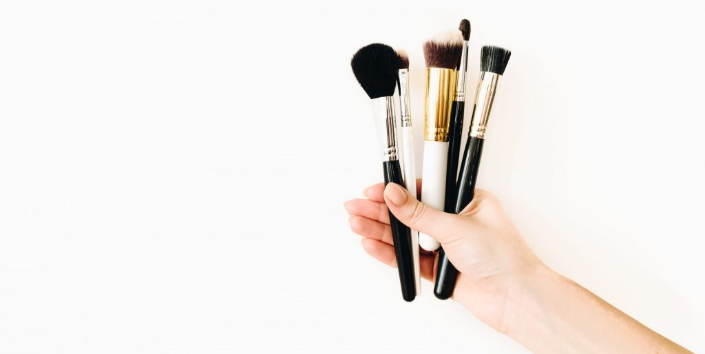 Various professional makeup brushes, held by a female caucasian MUA against white background
