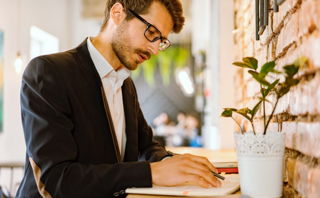 Man in black suit jacket writing on a notebook